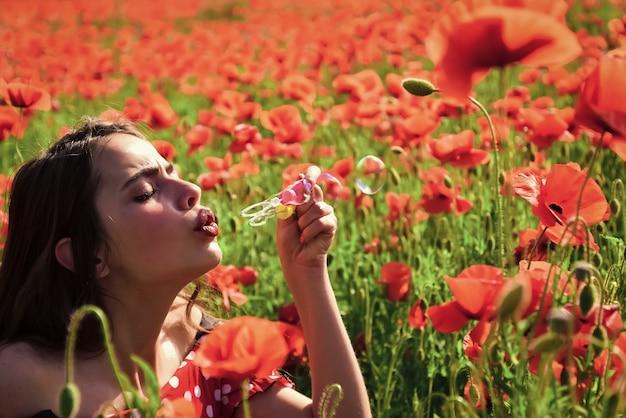 Poppy, verão, primavera, flor de papoula. mulher explodindo bolha em sonhos de campo de papoula