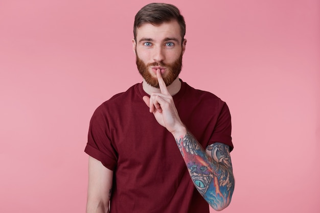 Poptrait de jovem barbudo com mão tatuada isolada sobre fundo rosa, com os olhos bem abertos, mantém o dedo da frente nos lábios, fica quieto, não faz barulho, demonstra gesto de silêncio.