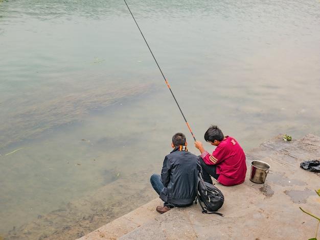 População chinesa desconhecida pescando no rio da cidade velha de fenghuang. a cidade antiga de phoenix ou condado de fenghuang é um condado da província de hunan, na china