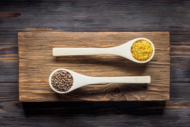 Populares asiáticos e europeus cereais vermelho lentilha lente culinaris e bulgur em culinária de madeira