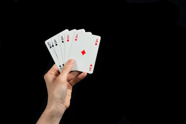 Pôquer de ases na mão isoladas no fundo preto