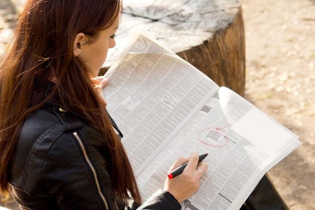 Por cima do ombro de uma jovem candidata a emprego lendo os anúncios classificados em um jornal
