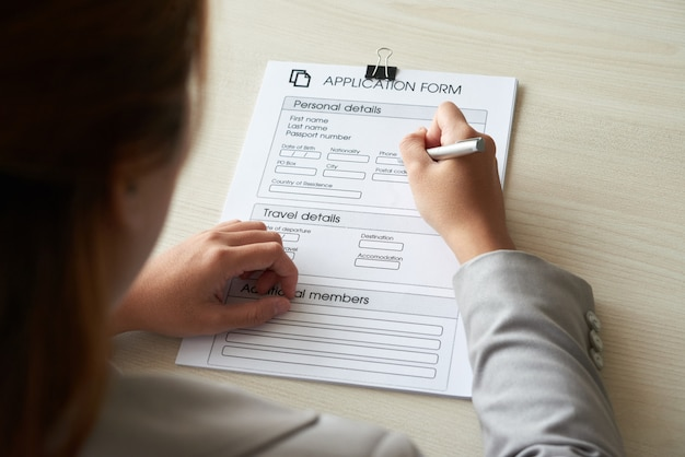 Por cima do ombro de uma mulher anônima preenchendo o formulário de inscrição