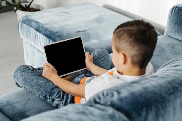 Por cima do ombro do menino usando um tablet digital