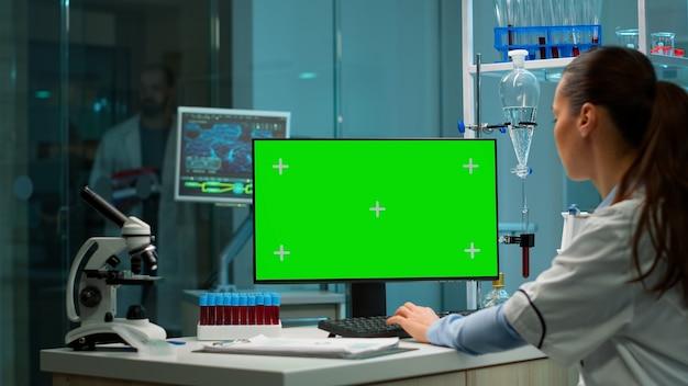 Por cima do ombro, tiro de químico trabalhando com modelo de mock-up de tela verde no computador desktop, display isolado, chroma key. no fundo, o doutor scietist entra no laboratório médico com amostra de sangue.