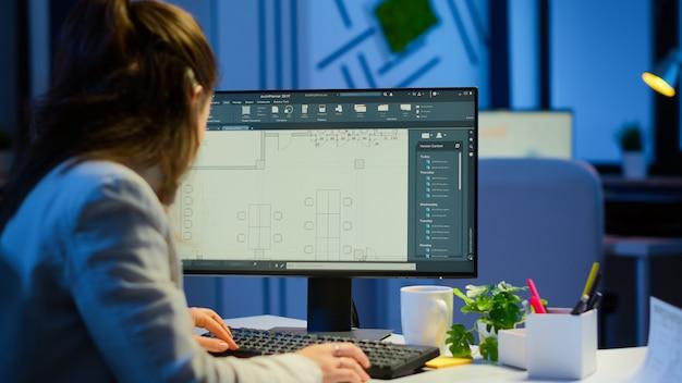 Por cima do ombro, tiro do engenheiro trabalhando com planos arquitetônicos, software cad no computador desktop. designer usando projetos de arquitetura de edifícios trabalhando horas extras, criando e estudando