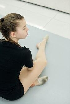Por cima do ombro, uma curiosa adolescente solitária sentada no chão assistindo ao ensaio na academia