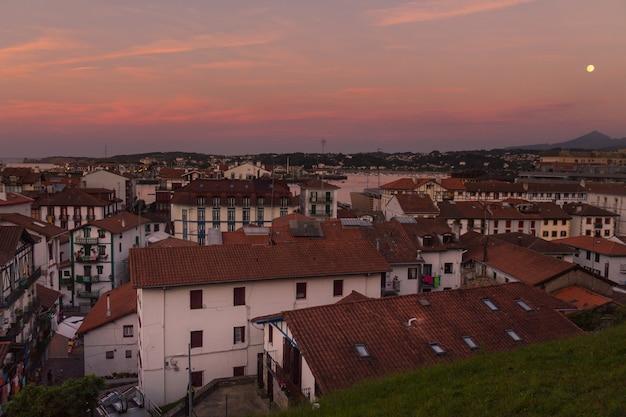 Pôr da lua sobre o pôr do sol em hondarribia, país basco.
