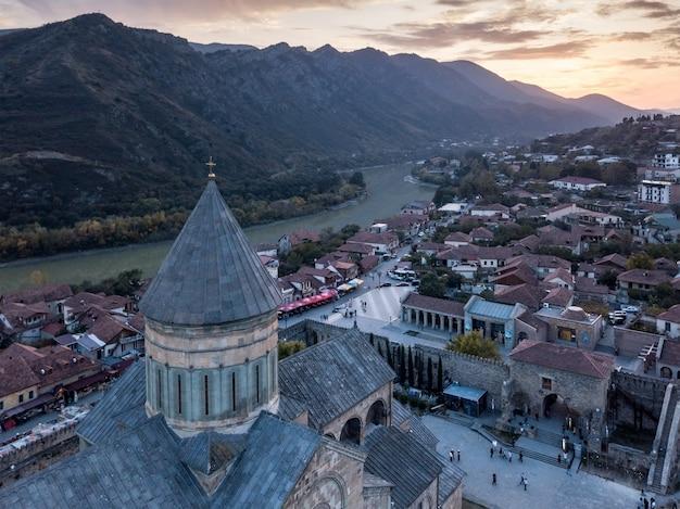Por do sol aéreo do tiro da catedral de svetitskhoveli no centro da cidade de mtskheta, geórgia.