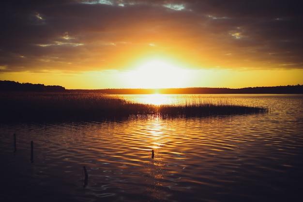Pôr do sol amarelo no lago. fundo desfocado natural, céu pôr do sol sobre o lago. silhueta da natureza