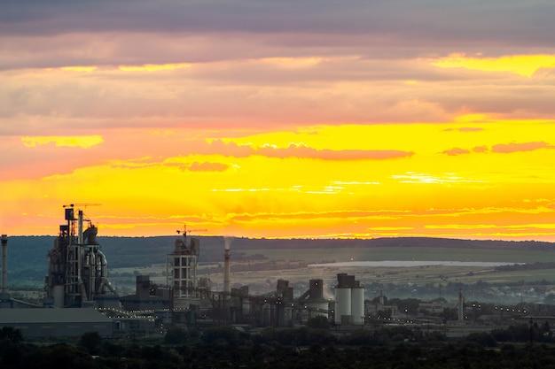 Por do sol amarelo sobre a paisagem industrial com chaminés de fábrica e tubos com fumaça poluindo a atmosfera.