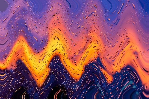 Pôr do sol ardente brilhante através de pingos de chuva na janela com luzes de bokeh