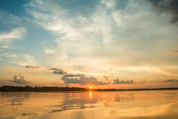 Por do sol bonito atrás das nuvens acima do fundo excedente da paisagem do lago.