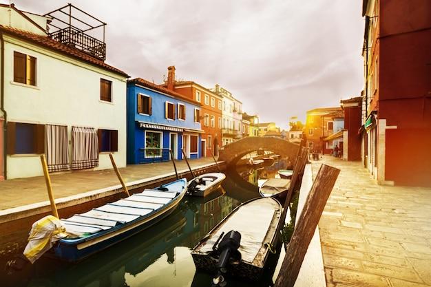 Por do sol bonito com barcos, edifícios e água. luz solar. tonificação. burano, itália.