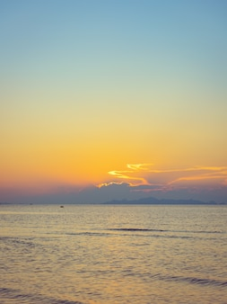 Por do sol bonito da praia com mar azul e a nuvem do céu claro dourado