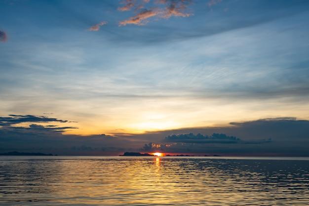 Por do sol bonito da praia com mar azul e fundo claro dourado da nuvem do céu