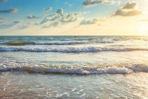 Pôr do sol bonito e onda do mar na praia de areia do horizonte