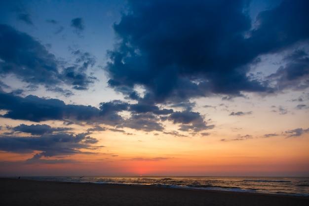 Por do sol bonito em uma praia arenosa vazia. céu dramático sob o mar.
