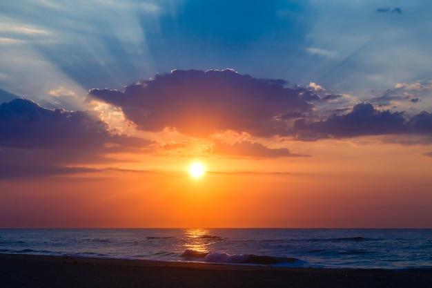 Por do sol bonito em uma praia arenosa vazia.