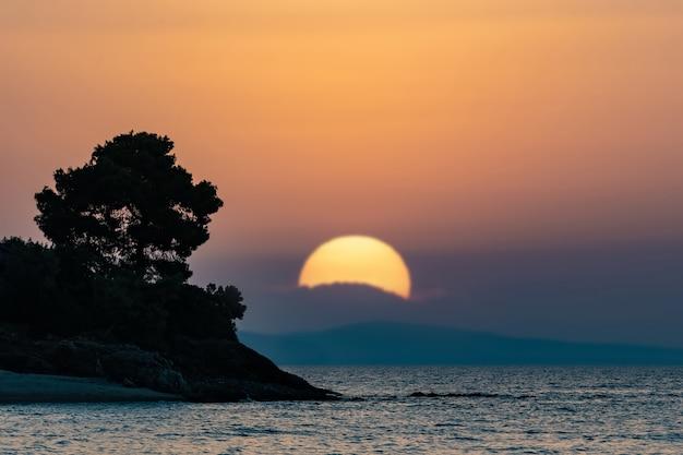 Pôr do sol brilhante com grande sol amarelo na superfície do mar com árvore de pedra