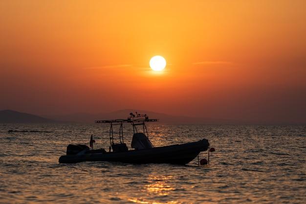 Pôr do sol brilhante com grande sol amarelo na superfície do mar