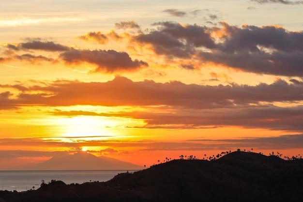 Pôr do sol coberto por silhuetas de montanhas com céu noturno e nuvens dramáticas