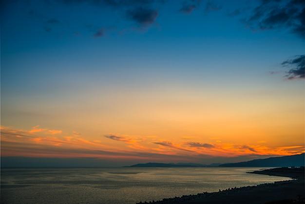 Por do sol colorido com fundo dramático do céu sobre o mar.
