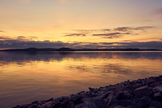 Pôr do sol colorido com reflexos na água e pedras de granito em primeiro plano