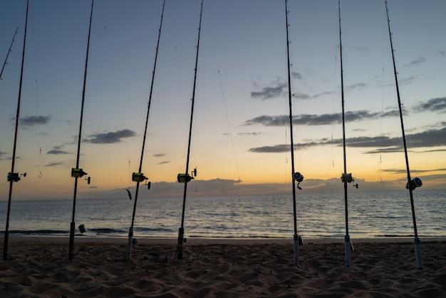 Pôr do sol colorido com vara de pescar no oceano. silhueta de pessoas e varas de pesca.