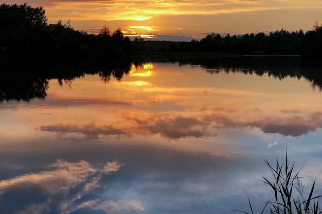 Pôr do sol colorido de verão no lago com nuvens refletidas na água