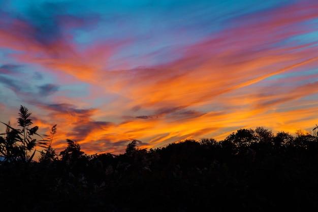 Pôr do sol colorido e brilhante no mar com belas nuvens