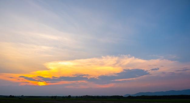 Pôr do sol colorido e nascer do sol com nuvens. cor azul e laranja da natureza. muitas nuvens brancas no céu azul. o tempo está claro hoje. pôr do sol nas nuvens. o céu é crepúsculo.