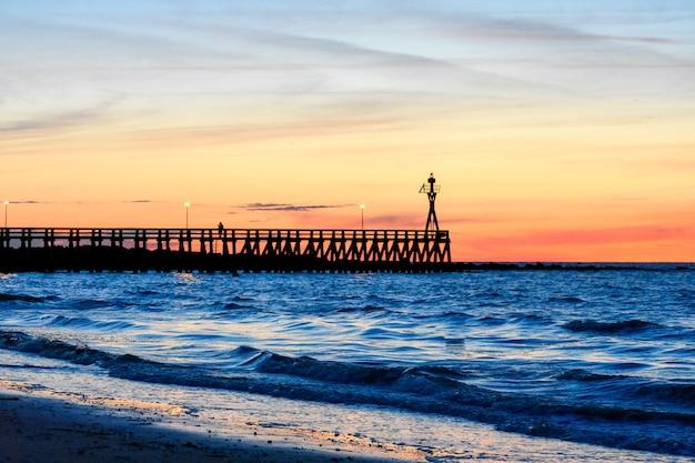 Pôr do sol colorido romântico no pontão de courseulles-sur-mer.
