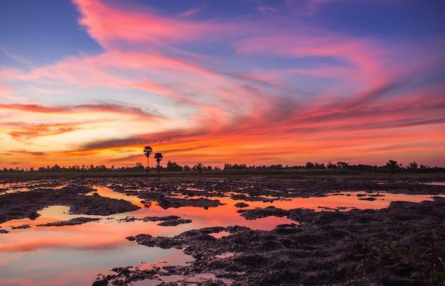 Por do sol colorido sobre a nuvem e o céu crepusculares, campo dramático colorido tailândia do céu.