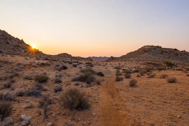 Por do sol colorido sobre o deserto de namib, aus, namíbia, áfrica. estrela do sol no horizonte, trilha que atravessa o deserto rochoso.