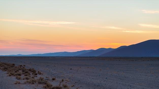 Por do sol colorido sobre o deserto de namib, namíbia, áfrica.