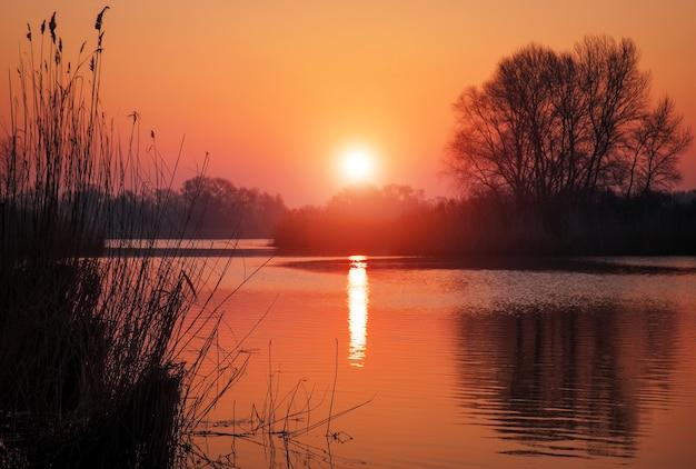 Pôr do sol colorido sobre o lago. céu vermelho e laranja. cena matinal