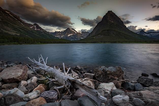 Por do sol colorido sobre o lago swiftcurrent no parque nacional de geleira, montana.