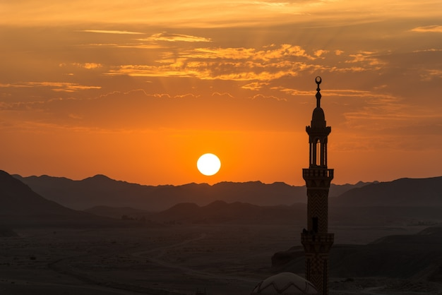 Pôr do sol com a mesquita musulmana em primeiro plano