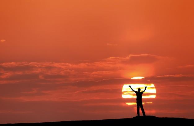 Pôr do sol com a silhueta de um homem com os braços levantados