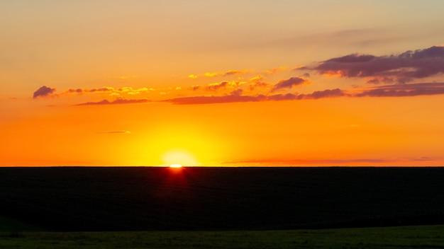 Pôr do sol com nuvens pitorescas sobre o campo