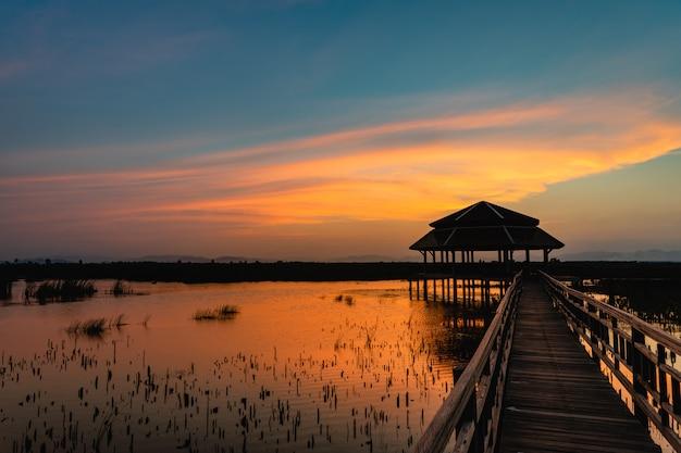 Por do sol com ponte de madeira e pavilhão no lago com nuvem e céu crepuscular no parque nacional de khao sam roi yot, tailândia.