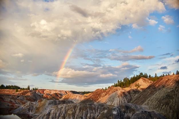 Pôr do sol com um arco-íris nas colinas de areia. conto de fadas