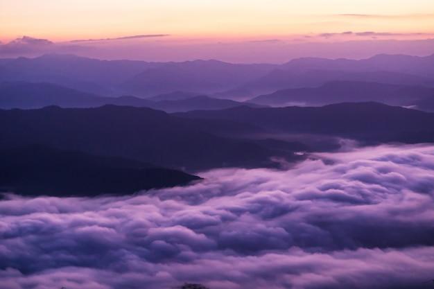 Pôr do sol com vista para as montanhas com névoa