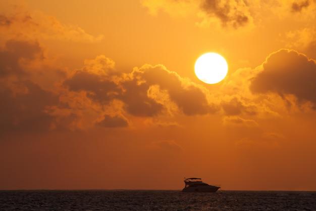 Pôr do sol com vista para o oceano com barcos