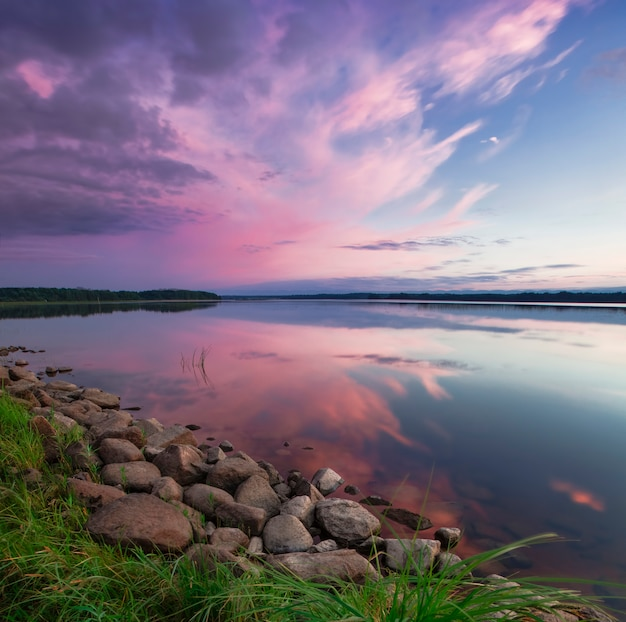 Por do sol cor-de-rosa no lago. noite, céu azul, refletido
