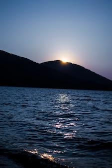 Pôr do sol da noite atrás da montanha em um grande lago vista romântica do pôr do sol no lago entre as ...