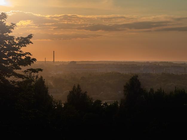 Pôr do sol da noite com vistas da cidade ao longe.