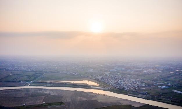 Pôr do sol de campos com vários tipos de agricultura e vilas ao lado com poluição do ar no inverno, tainan, taiwan, vista aérea
