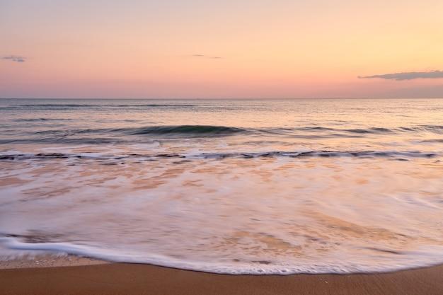 Pôr do sol de cor pastel suave na praia tropical.